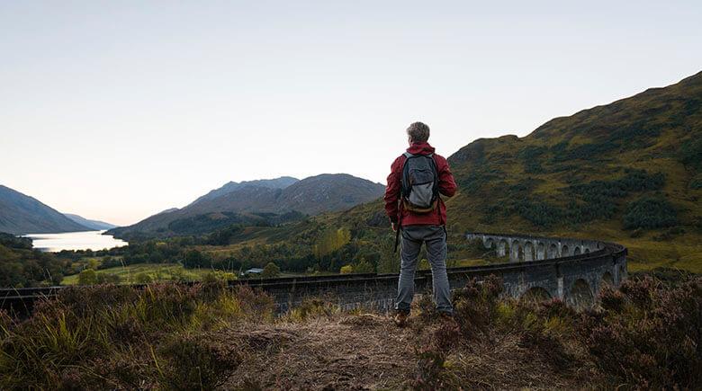 Mann steht am Viadukt in Schottland